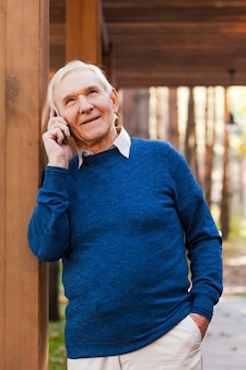 Estou tão feliz em ouvir de você! homem sênior feliz falando no celular e sorrindo enquanto fica ao ar livre