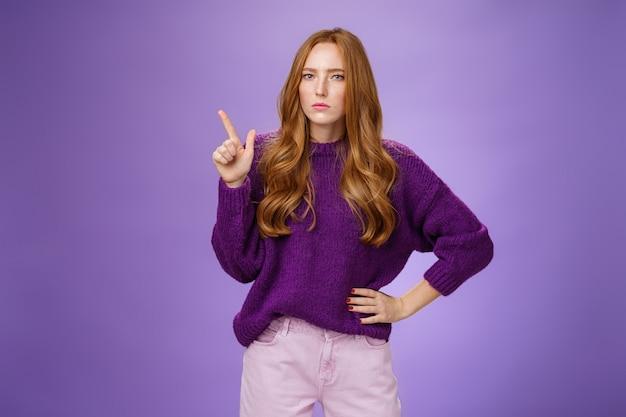 Estou te observando. retrato da irmã ruiva fofa mandona e desconfiada, de suéter roxo, apertando os olhos, duvidoso e sério, fazendo suposições ou hesitando, apontando para o canto superior esquerdo.