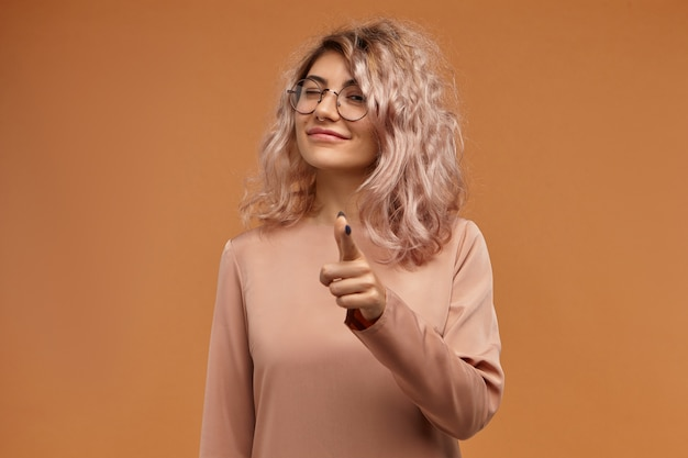 Estou te observando. retrato horizontal de alegre brincalhão jovem mulher branca usando elegantes óculos redondos e piercing no nariz, apontando o dedo indicador para a câmera e piscando. linguagem corporal