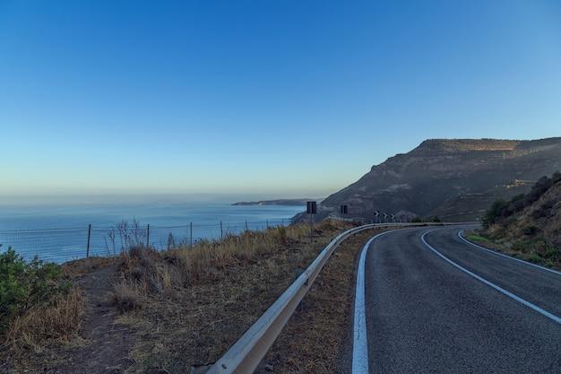 Estrada à beira-mar com céu azul em dia claro.