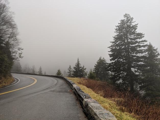 Estrada ao redor das montanhas em um dia de nevoeiro