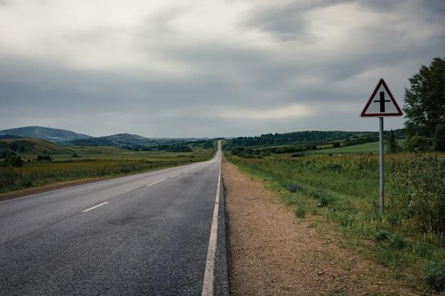 Estrada asfaltada à linha do horizonte sob um céu nebuloso.