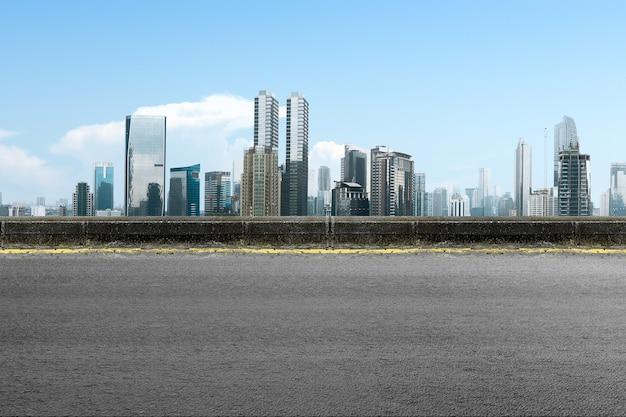 Estrada asfaltada com edifício moderno e arranha-céus no centro