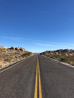 Estrada asfaltada com linhas amarelas sob um céu azul claro