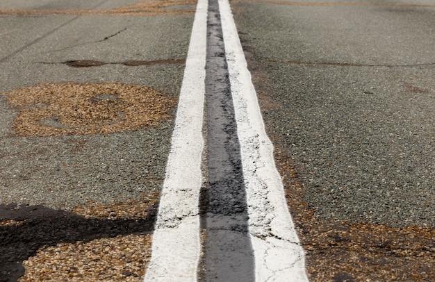 Estrada asfaltada com linhas de marcação listras brancas.
