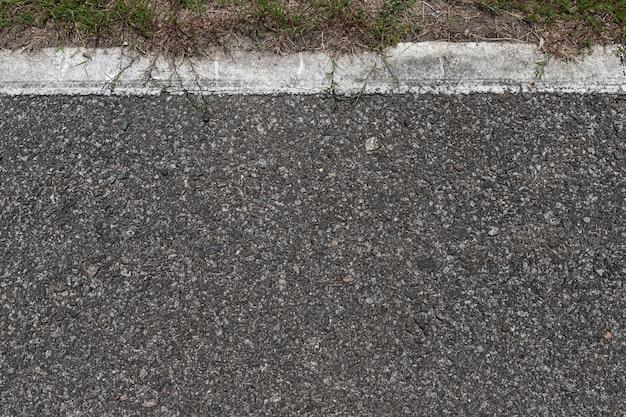 Estrada asfaltada com listras e fundo da textura da grama verde, espaço vazio da cópia.