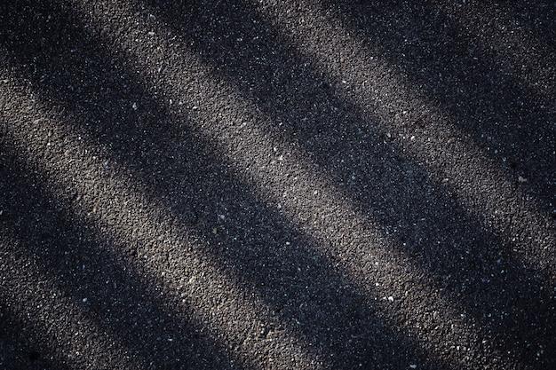Estrada asfaltada com uma sombra escura da cerca. as listras abstratas são claras e escuras.