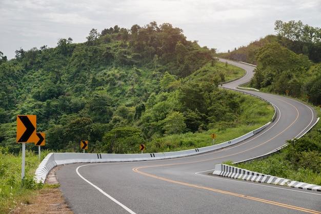 Estrada asfaltada curvada com curvas do sinal nas montanhas.