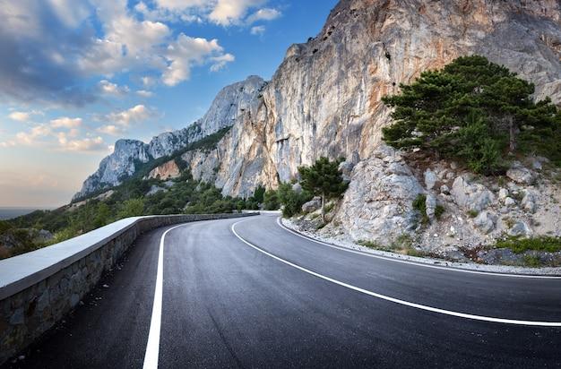 Estrada asfaltada na floresta de verão ao pôr do sol. montanhas da crimeia