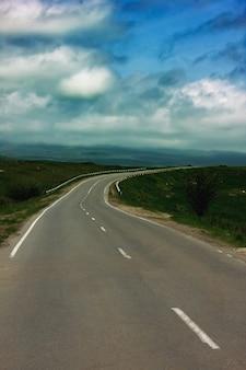 Estrada asfaltada no meio de um campo de verão