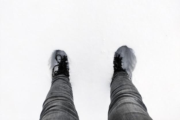 Estrada branca não desobstruída coberta de neve com pegadas humanas profundas.