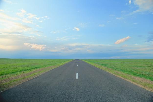 Estrada cercada por campos de grama sob um céu azul