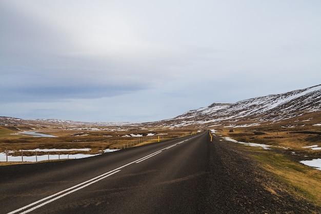 Estrada cercada por colinas cobertas de neve e vegetação sob um céu nublado na islândia