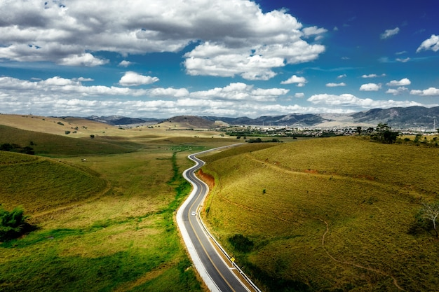 Estrada cercada por colinas cobertas de vegetação com montanhas sob um céu nublado