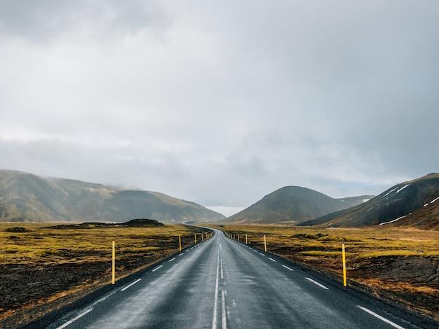 Estrada cercada por colinas cobertas de vegetação e neve sob um céu nublado na islândia