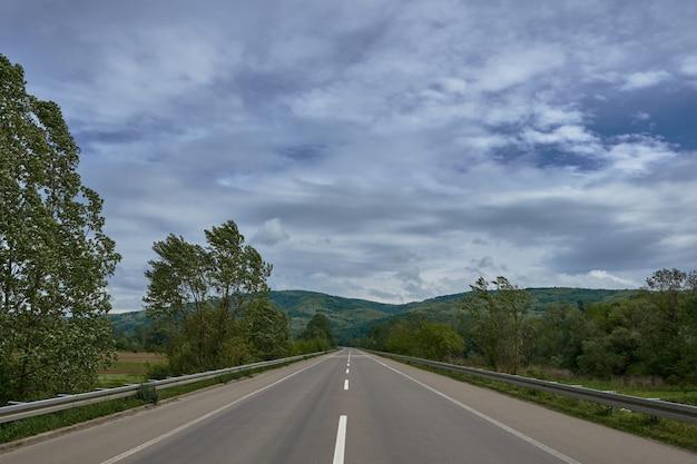Estrada cercada por colinas cobertas por florestas sob o céu nublado durante o dia