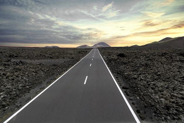 Estrada cercada por colinas e pedras durante o pôr do sol no parque nacional de timanfaya, na espanha