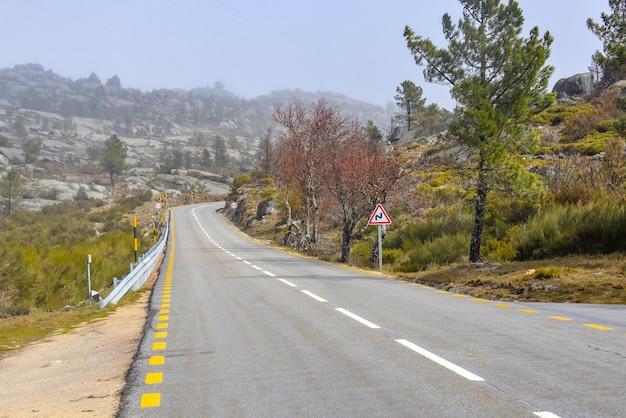 Estrada cercada por pedras e vegetação coberta pela névoa durante o dia