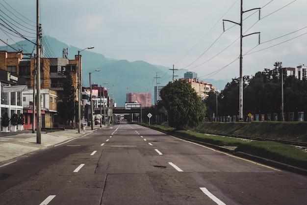 Estrada cercada por vegetação e edifícios com montanhas sob a luz do sol