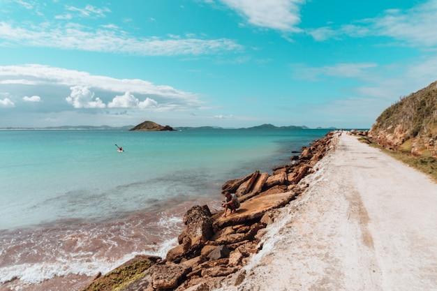 Estrada coberta de areia cercada de mar e pedras sob um céu azul no rio de janeiro