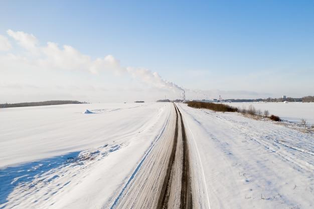 Estrada coberta de neve de uma fábrica com cachimbos