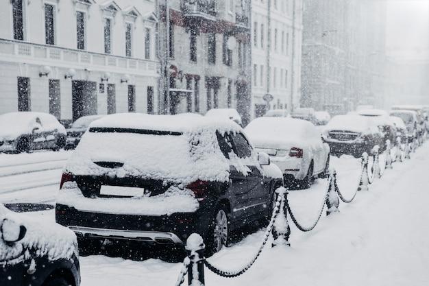 Estrada coberta de neve e transporte. cidade paralisada após uma forte nevasca. carros cobertos de neve espessa
