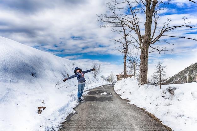 Estrada coberta de neve na floresta entre montanhas