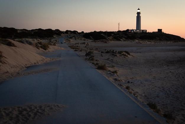 Estrada, coberto areia, de, a, dunas, estrada, direção, farol, de, trafalgar, cadiz, espanha, em, pôr do sol