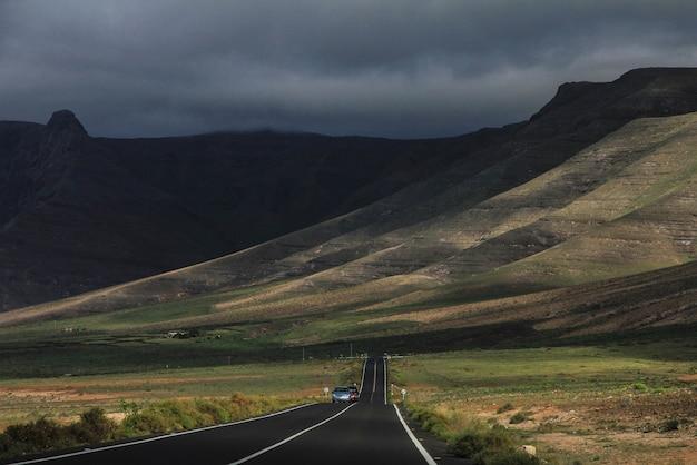 Estrada com carros dirigindo à distância no meio de campos gramados e montanhas ao fundo