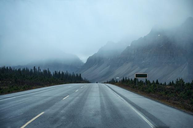 Estrada com montanha rochosa em dia sombrio no parque nacional de banff
