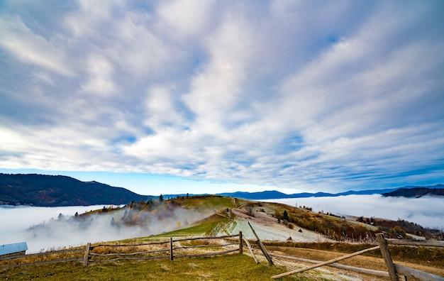 Estrada congelada coberta de geada branca contra um lindo céu azul e névoa branca e fofa