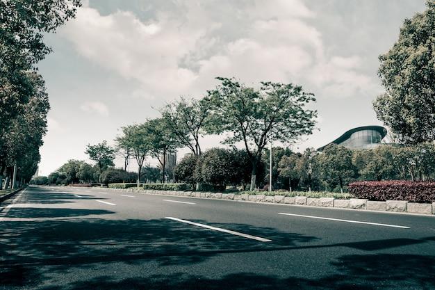 Estrada curva vazia, céu azul e nuvens