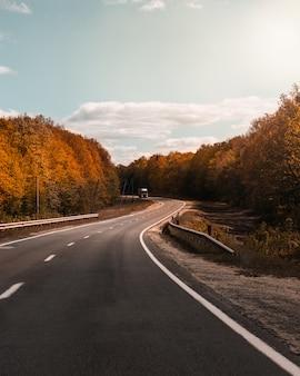 Estrada curvada com árvores quentes de outono nos lados