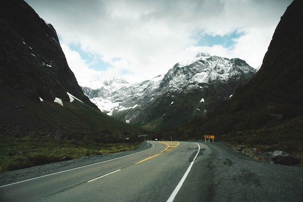 Estrada curvilínea no campo com montanhas nevadas e belas nuvens no céu