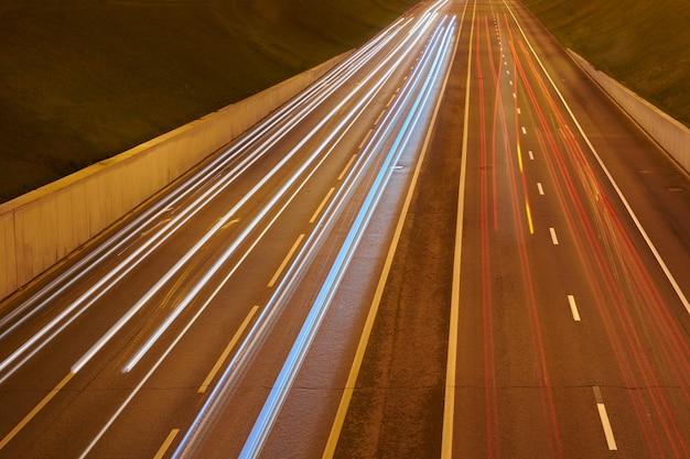Estrada da estrada à noite com luzes de carros. trilha de luz amarela e vermelha na estrada com tráfego de velocidade. fundo urbano abstrato de longa exposição