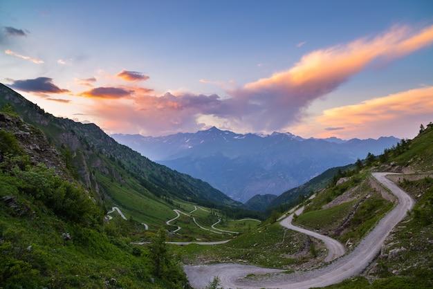 Estrada da montanha da sujeira que conduz à passagem de montanha alta em itália.