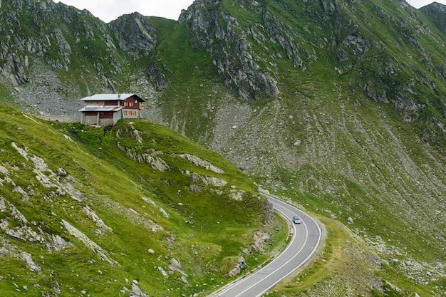 Estrada da montanha de transfagarasan com o edifício pequeno na rocha, carpathians romenos