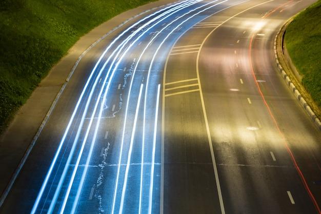 Estrada da noite com as raias claras do carro. listras de pintura luz à noite.