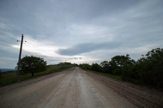 Estrada de areia para as nuvens estrada de areia branca para o céu nublado e grama verde ao lado