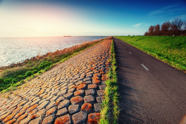 Estrada de asfalto ao longo do mar ao pôr do sol