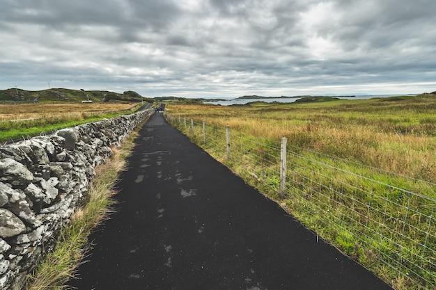 Estrada de asfalto ao longo dos campos. irlanda do norte.