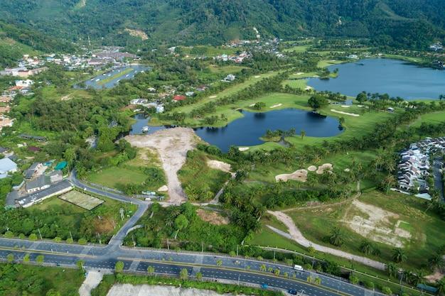 Estrada de asfalto ao redor do campo de golfe verde foto por vista aérea drone tiro