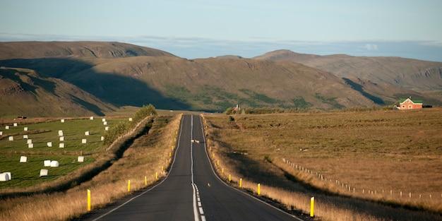 Estrada de asfalto através da terra e fardos de feno, levando a montanhas