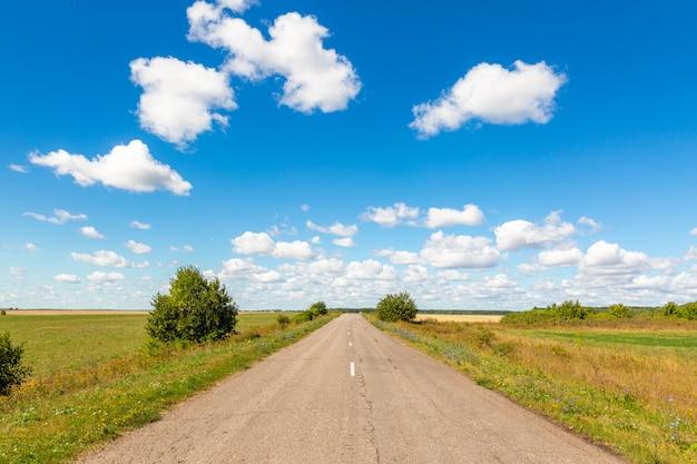 Estrada de asfalto através do campo verde e nuvens no céu azul