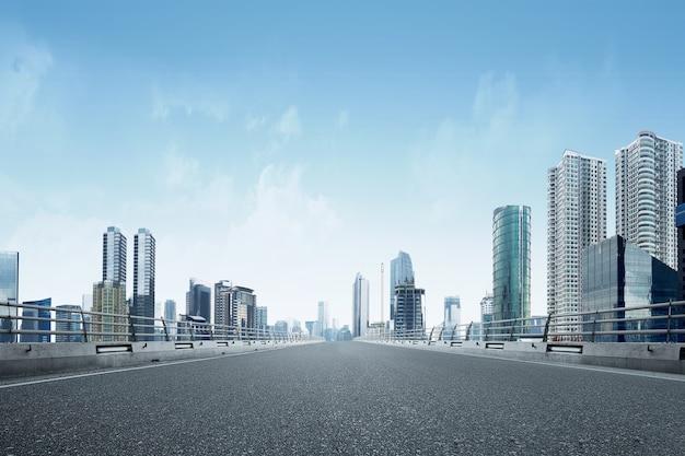 Estrada de asfalto com edifício moderno e arranha-céus