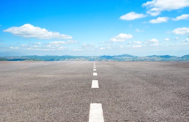 Estrada de asfalto com linhas de marcação textura de listras brancas e fundo de céu azul