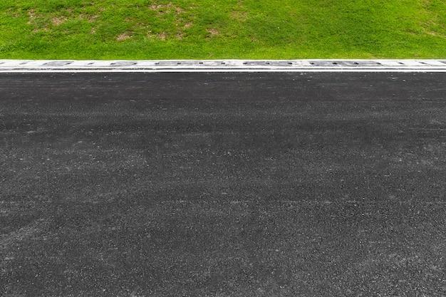 Estrada de asfalto com listras e textura de grama verde