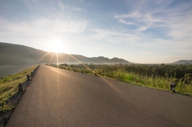 Estrada de asfalto com reservatório no céu azul claro e montanhas