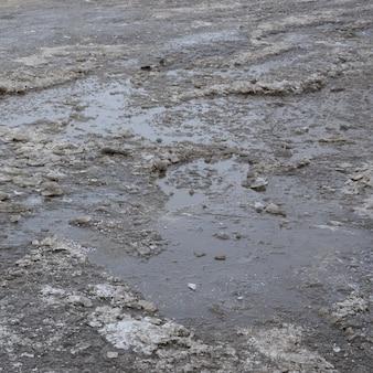 Estrada de asfalto danificada com buracos causados por ciclos de congelamento e descongelamento durante o inverno