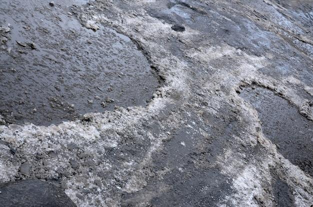 Estrada de asfalto danificado com buracos causados pelo congelamento
